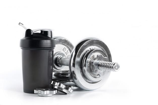 Whey proteína shaker garrafa com haltere de placa de cromo isolado no fundo branco, equipamentos de fitness Foto Premium
