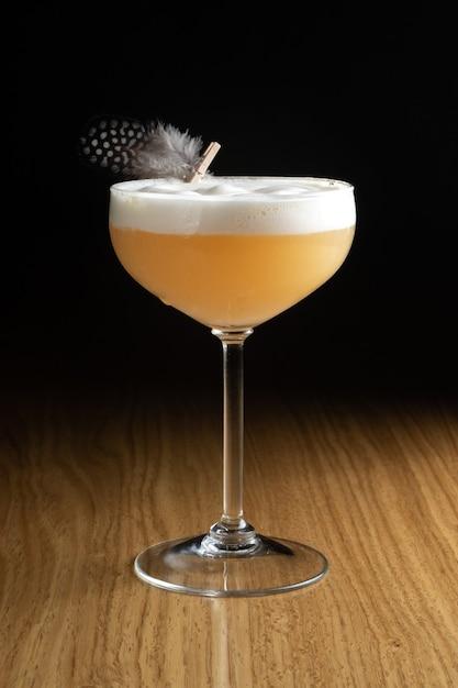 Whiskey sour é um coquetel alcoólico à base de uísque e suco de limão, decorado com uma pena de codorna em um vidro transparente sobre uma mesa de madeira. Foto Premium