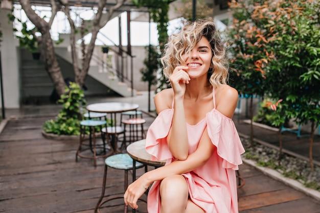 Winsome loira garota em um vestido romântico sentado no café de rua. jovem entusiasmada posando em um restaurante com plantas Foto gratuita