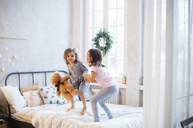 Wo meninas, irmãs lutando travesseiros na cama, a janela decorada com uma guirlanda de natal, vida, infância Foto Premium