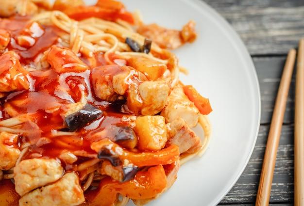 Wok macarrão udon com frango e legumes em um prato branco, close-up Foto Premium