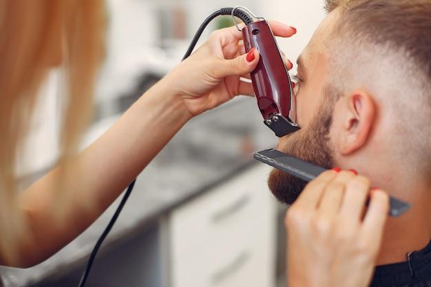 Woma barbear barba de homem em uma barbearia Foto gratuita
