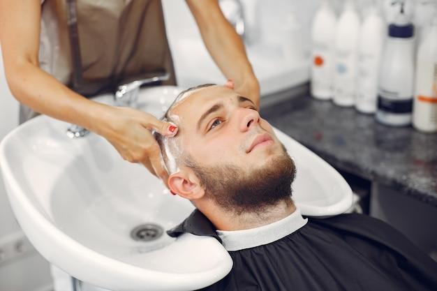 Woma lavando a cabeça do homem em uma barbearia Foto gratuita