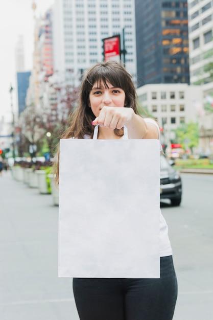 Wonan segurando a sacola de compras branca na mão Foto gratuita