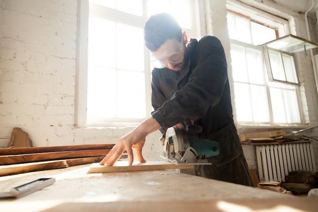 Woodworker trabalha na produção local de madeira Foto gratuita