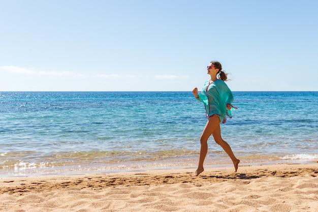 Wooman que corre na praia em um dia ensolarado. garota verão praia Foto Premium