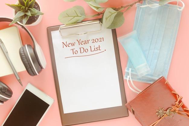 Word new year 2021 to do list na área de transferência com papelaria, máscara e desinfetante para as mãos. conceito para apresentar a lista de tarefas no ano novo de 2021, nova pandemia pós-covid-19 normal. Foto Premium