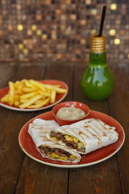 Wrap de doner de carne em pão sírio servido com batata frita e maionese Foto gratuita