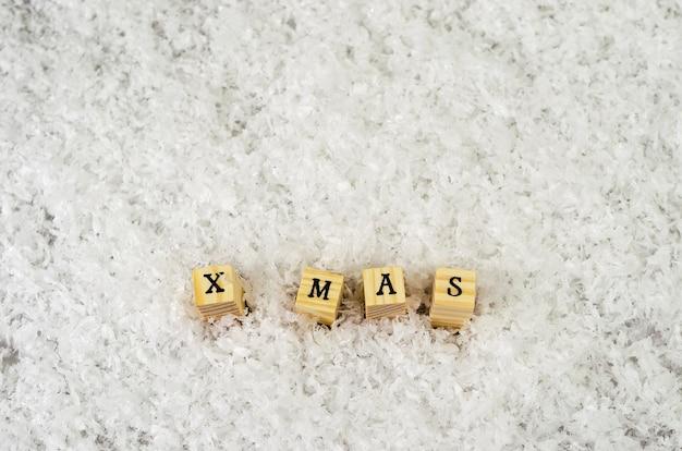 X mas palavra feita de letras em cubos de madeira na neve Foto Premium
