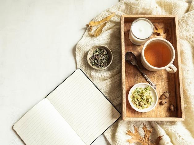 Xadrez de malha, xícara de chá de ervas e bloco de notas aberto Foto Premium