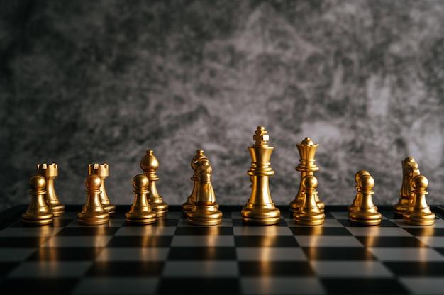 Xadrez de ouro no jogo de tabuleiro de xadrez para o conceito de liderança de metáfora de negócios Foto gratuita