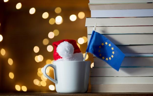 Xícara branca e chapéu de natal com a bandeira da união da europa Foto Premium