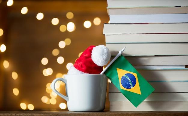Xícara branca e chapéu de natal com bandeira do brasil perto de livros Foto Premium