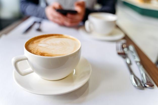 Xícara com café na mesa de uma cafeteria. homem usando um telefone Foto Premium