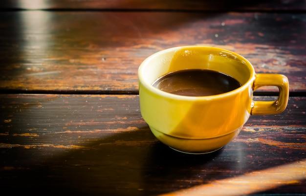 Xícara de café amarelo na velha mesa de madeira entre a luz do sol Foto Premium
