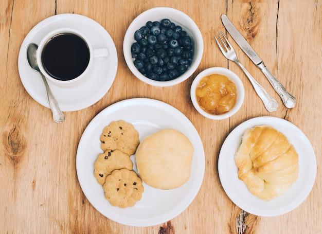 Xícara de café; amoras; geléia; pão; pão e biscoitos na mesa Foto gratuita