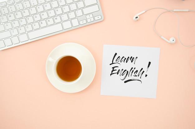 Xícara de café ao lado para aprender mock-up inglês nota auto-adesiva Foto gratuita