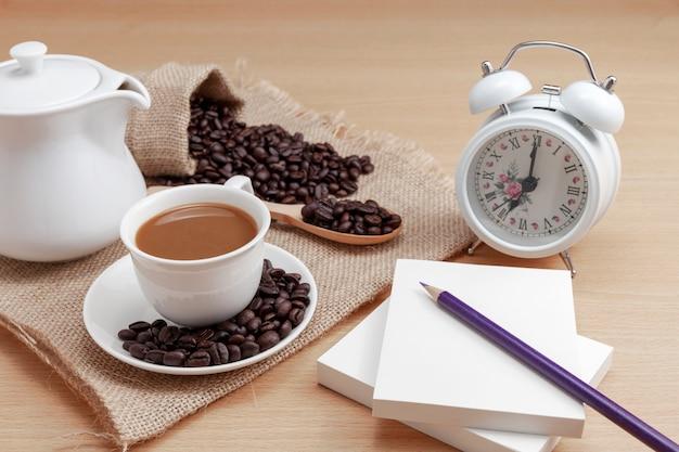 Xícara de café branca com grãos de café e despertador em fundo de madeira Foto Premium