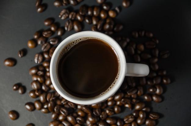 Xícara de café branca com grãos de café na vista superior Foto Premium