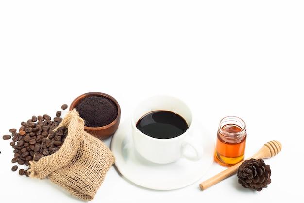 Xícara de café branca e grãos de café mel no fundo branco Foto Premium