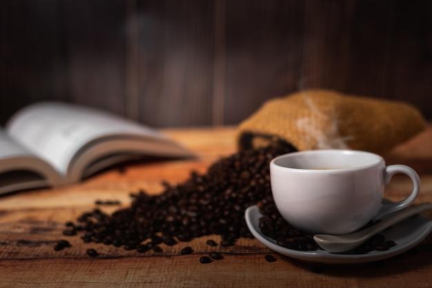 Xícara de café branca e grãos de café Foto Premium