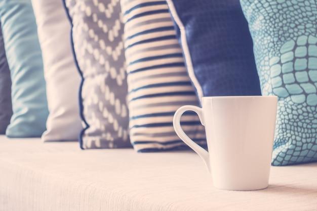 Xícara de café branca no sofá com decoração de almofadas no interior da sala de estar Foto gratuita