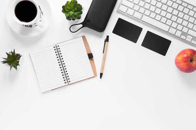 Xícara de café; cacto vegetal; cartão; maçã; diário e caneta no pano de fundo branco Foto gratuita