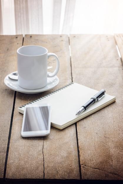 Xícara de café, caderno, caneta e telefone inteligente Foto Premium