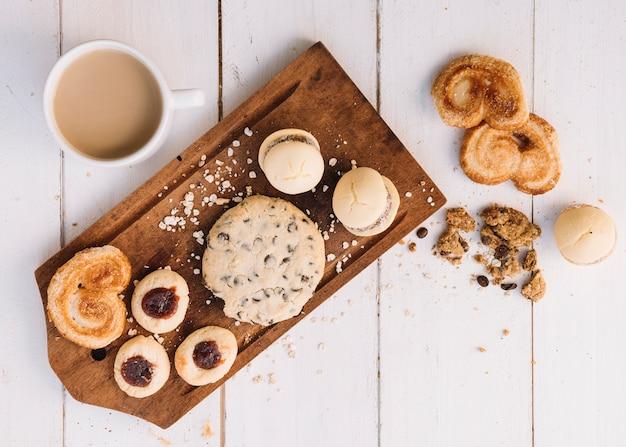 Xícara de café com biscoitos na placa de madeira Foto gratuita