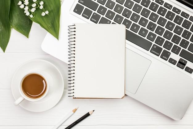 Xícara de café com bloco de notas em espiral no laptop com lápis de cor na mesa de escritório de madeira Foto gratuita