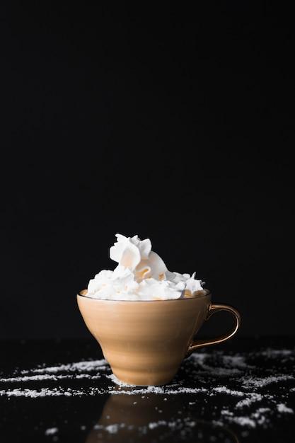 Xícara de café com chantilly na superfície preta Foto gratuita