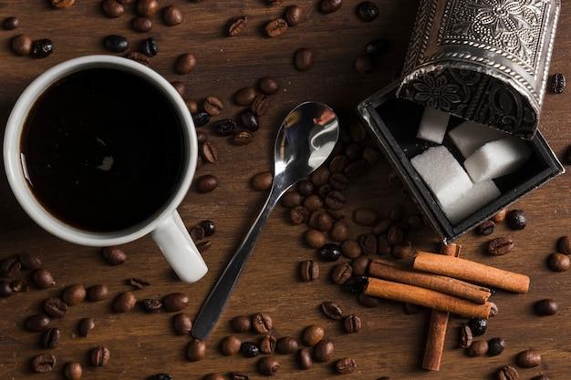 Xícara de café com colher perto de caixa de açúcar e canela em pau Foto gratuita