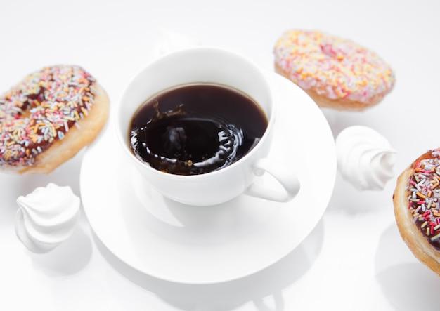 Xícara de café com donuts e merengues em movimento Foto Premium