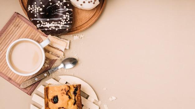 Xícara de café com donuts e torta na mesa Foto gratuita