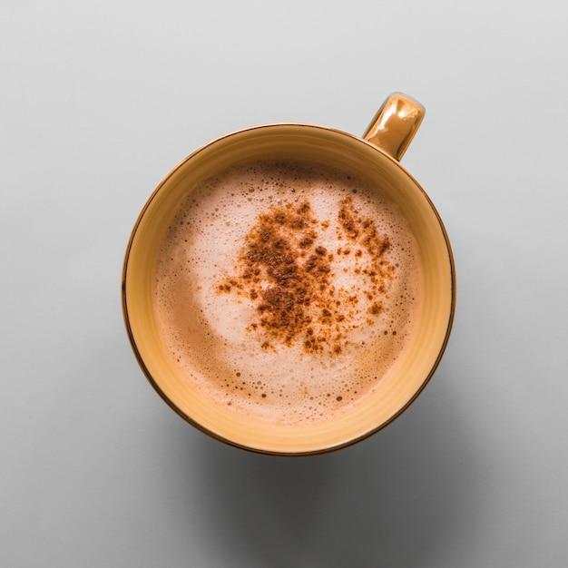 Xícara de café com espuma de leite e cacau em pó no fundo cinza Foto gratuita
