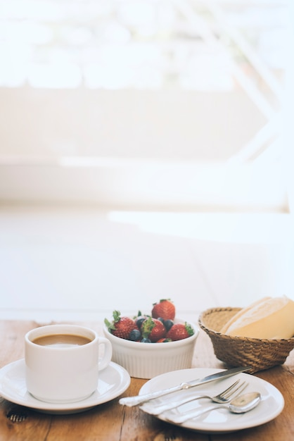Xícara de café com frutas frescas e talheres na placa contra o fundo de madeira Foto gratuita