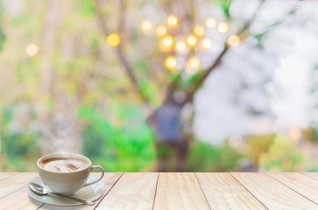 Xícara de café com fumaça e colher no terraço de madeira branco sobre desfocagem o bokeh de luz Foto gratuita