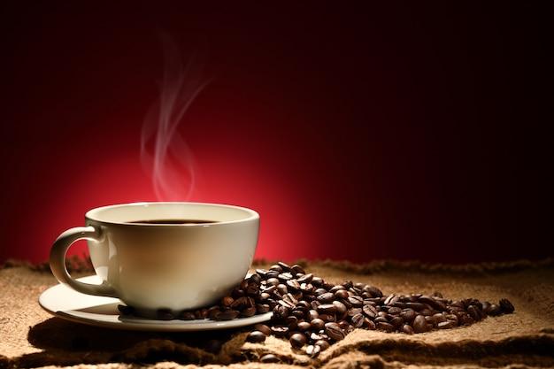 Xícara de café com fumaça e grãos de café sobre fundo marrom avermelhado Foto Premium