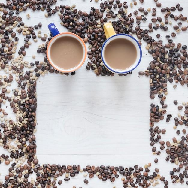 Xícara de café com grãos de café crus e torrados no fundo de madeira Foto gratuita