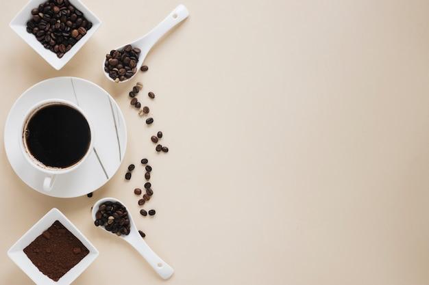 Xícara de café com grãos de café e pó de café sobre fundo bege Foto gratuita