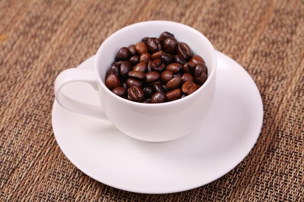 Xícara de café com grãos de café frescos em um fundo marrom Foto Premium