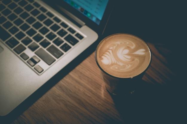 Xícara de café com leite bem feito ao lado de um laptop Foto gratuita