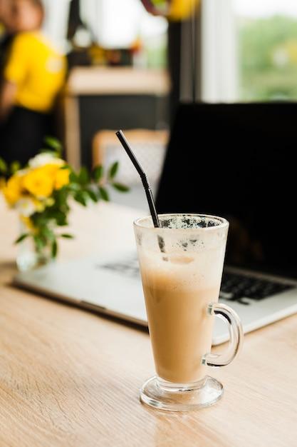 Xícara de café com leite com canudo na frente da desfocagem laptop na mesa Foto gratuita