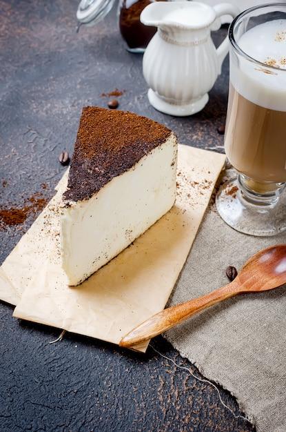 Xícara de café com leite com um pedaço de queijo no café moído Foto Premium