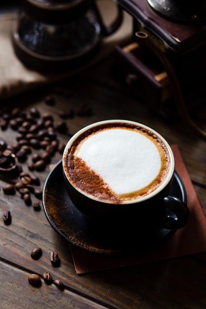 Xícara de café com leite e grãos de café com gotejador de café em conjunto na mesa de madeira. Foto Premium