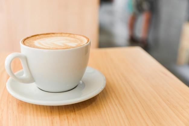 Xícara de café com leite em um café cappuccino na mesa de madeira Foto gratuita