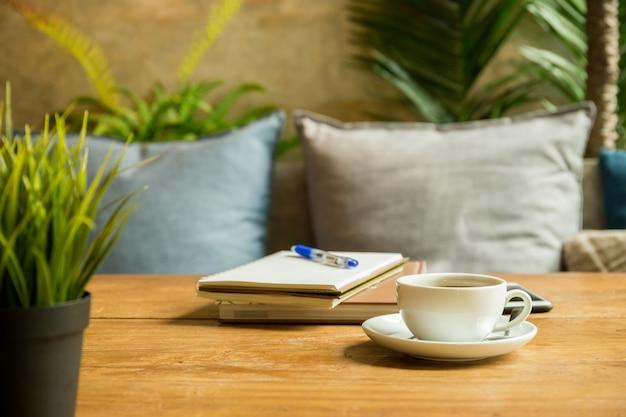 Xícara de café com livros e pena na tabela de madeira na cafetaria. Foto Premium