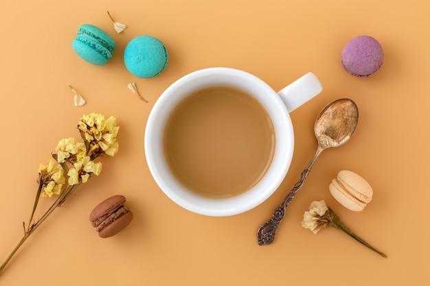 Xícara de café com macaroons, flor e colher vintage, lay plana Foto Premium