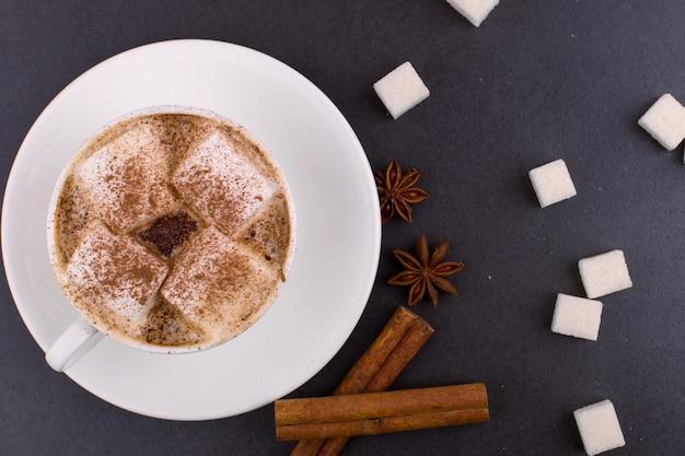 Xícara de café com marshmallows e cacau, açúcar, canela e anis estrelado, sobre um fundo cinza de pedra. Foto Premium