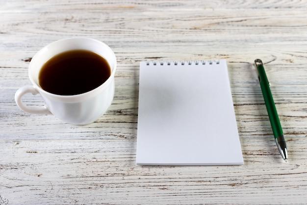 Xícara de café com notebook na mesa de madeira, vista de cima, copie o espaço Foto Premium
